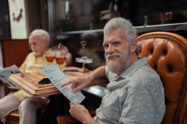 Obiad z przyjacielem. brodaty starszy mężczyzna wybierający danie podczas obiadu z przyjacielem