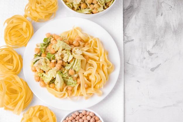 Obiadowy makaron wegetariański z sałatą i ciecierzycy na szarym tle.