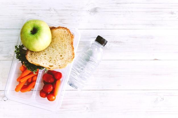 Obiadowy pudełko z warzywami i plasterkiem chleb dla zdrowego szkolnego lunchu na drewnianym stole