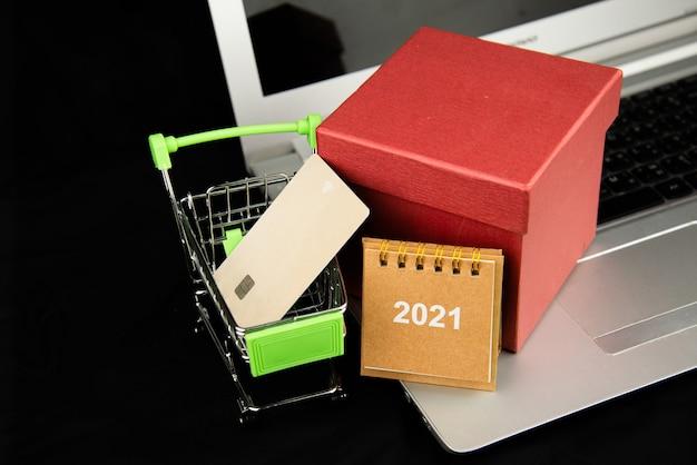 Obiekt grupowy kalendarz 2021 i karta kredytowa w koszyku i czerwone pudełko gitf na laptopie z ciemnym tłem.