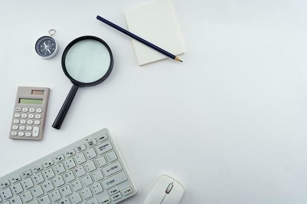 Obiekty biznesowe komputera pc, klawiatury, myszy, ołówka, kompasu i kalkulatora, szkło powiększające na tle białego stołu.