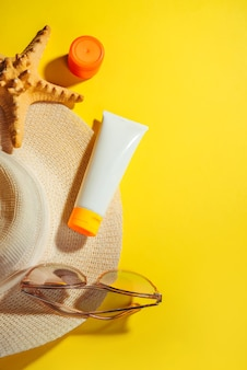 Obiekty chroniące przed słońcem, filtry przeciwsłoneczne. słomkowy kapelusz damski z okularami przeciwsłonecznymi i kremem ochronnym spf flat leżał na żółtym tle. akcesoria plażowe. koncepcja wakacji letnich podróży