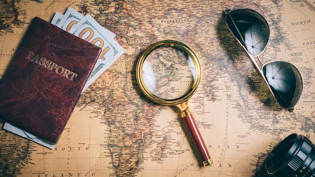 Obiekty podróżników leżą na mapie świata w stylu vintage, widok z góry. koncepcja planowania podróży.