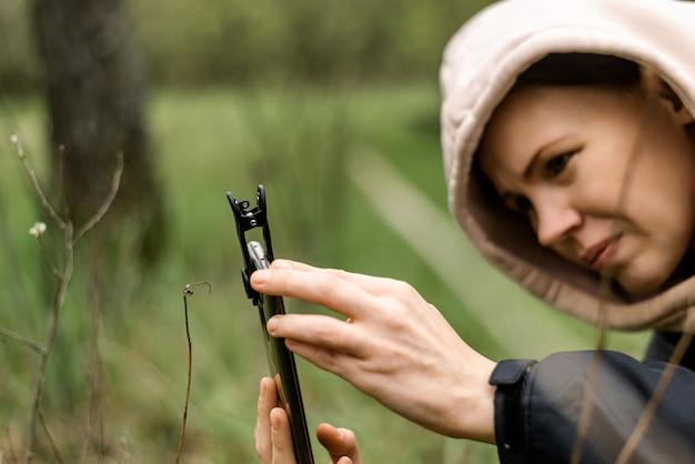 Obiektywy do telefonów do makrofotografii. kobieta trzyma w dłoni telefon komórkowy z przystawką do makrofotografii i robi zdjęcia roślinom.