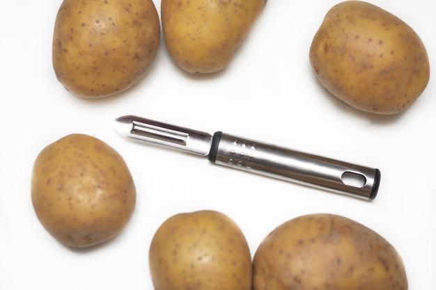 Obieraczka do ziemniaków na białym tle wśród ziemniaków. naczynia kuchenne, narzędzia kuchenne. zdjęcie z bliska
