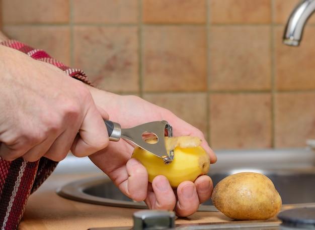 Obieranie ziemniaka obieraczką w kuchni. ścieśniać