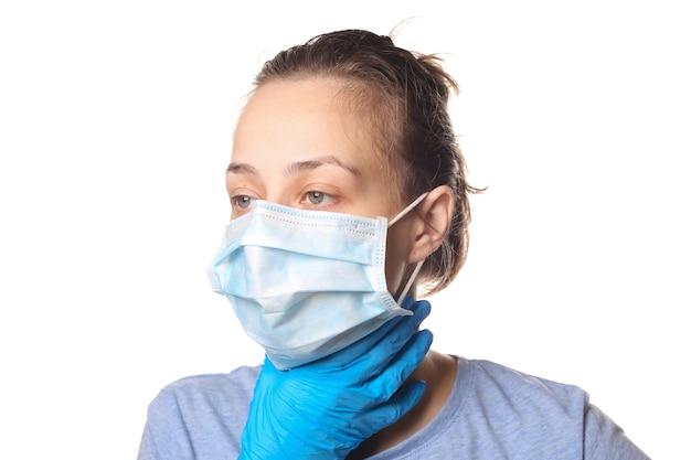 Objawy grypy. kobieta w masce medycznej trzyma gardło na białym tle. ból gardła.