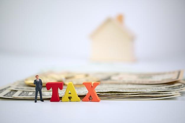 Oblicza biznesmen pozycję obok drewna podatku słowa na banknocie, złotej monecie i drewnianym domu