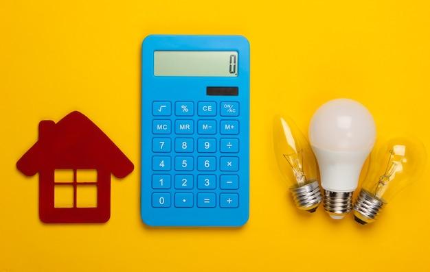Obliczanie efektywności energetycznej i kosztów. kalkulator, figurka domu, żarówki na żółto.
