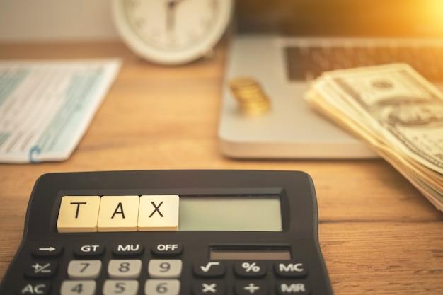 Obliczanie i płacenie tła koncepcji podatku. pulpit biznesowy z 1040 formularzami wniosków, kalkulatorem, laptopem i rachunkami dolarowymi. zdjęcie biznesowe