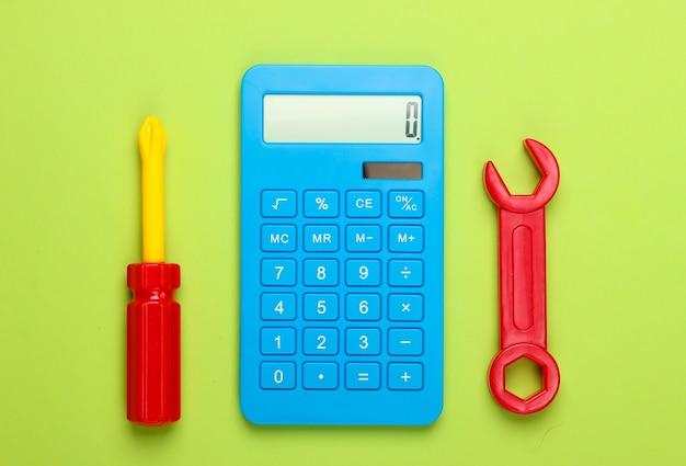 Obliczanie kosztów prac naprawczych. kalkulator i zabawka klucz i śrubokręt na zielonym tle. widok z góry