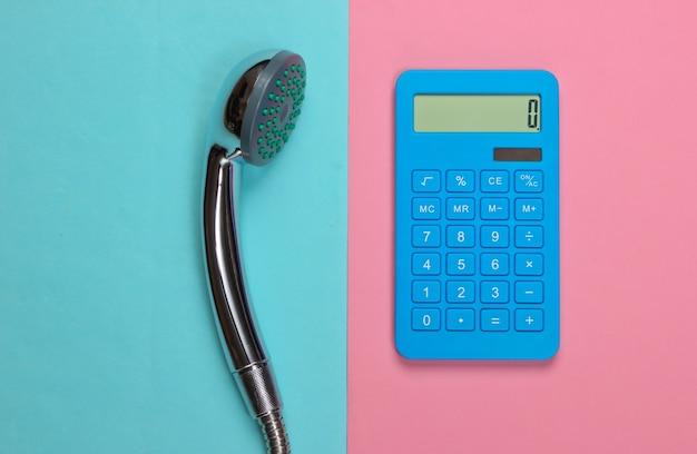 Obliczanie kosztów wody. kalkulator i głowica prysznicowa na różowo-niebieskim pastelu