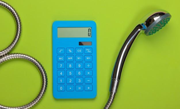 Obliczanie kosztów wody. kalkulator i głowica prysznicowa z wężem na zielono