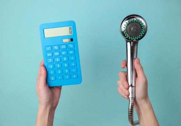Obliczanie kosztów wydatków na wodę. ręka trzyma głowicę prysznicową i kalkulator na niebiesko.