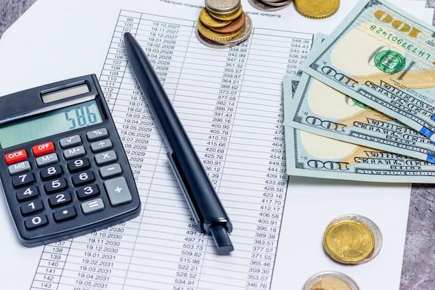 Obliczanie płatności hipotecznych i pożyczkowych za pomocą kalkulatora i banknotów na szarym tle