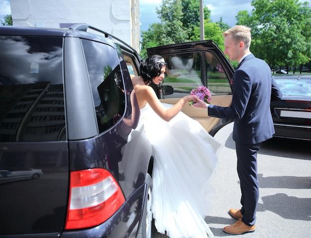 Oblubieniec pomaga pannie młodej wydostać się z samochodu dla nowożeńców