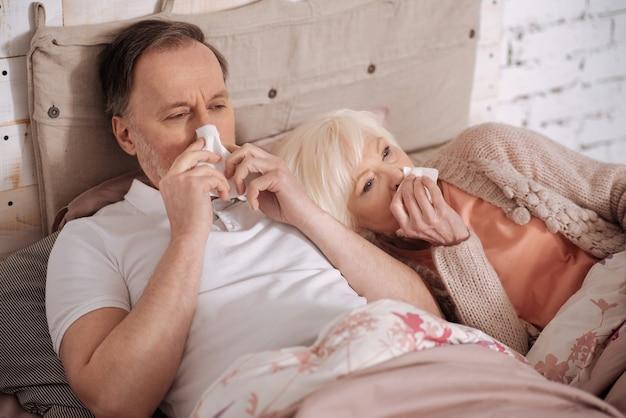 Oboje chorzy. starszy chory para leży na łóżku i wieje nos.
