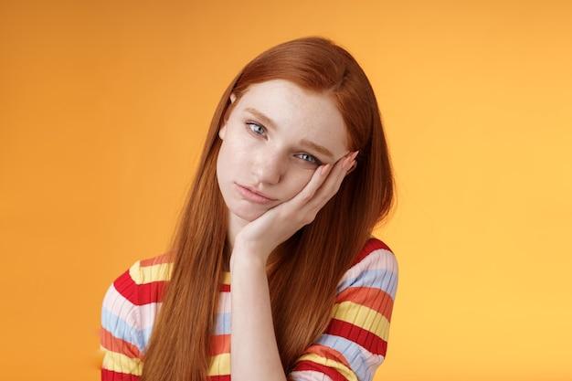 Obojętna, beztroska, senna ruda, głupia studentka szczupła dłoń wyglądająca na znudzoną niezainteresowaną słuchaj kiepskich historii chcą uciec stojąc wyczerpany i pozbawiony zainteresowania, na pomarańczowym tle.