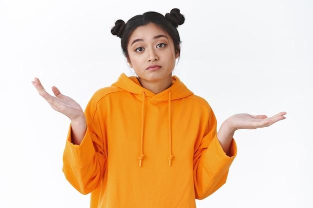 Obojętna młoda koreańska dziewczyna wzrusza ramionami i rozkłada ręce, wygląda na nieostrożną, nie zawraca sobie głowy, nie przejmuje się i nie interesuje tym, co się dzieje, stoi na białej ścianie