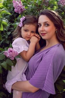 Obok bzu stoi dziewczyna z mamą w liliowych sukienkach