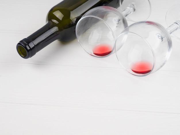 Obok dwóch kieliszków z resztkami czerwonego wina leży butelka wina