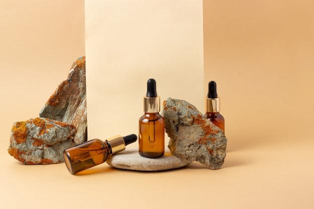 Obok kamienia stoi bursztynowa butelka na olejki eteryczne i kosmetyki. szklana butelka. zakraplacz, butelka z rozpylaczem. koncepcja kosmetyków naturalnych.