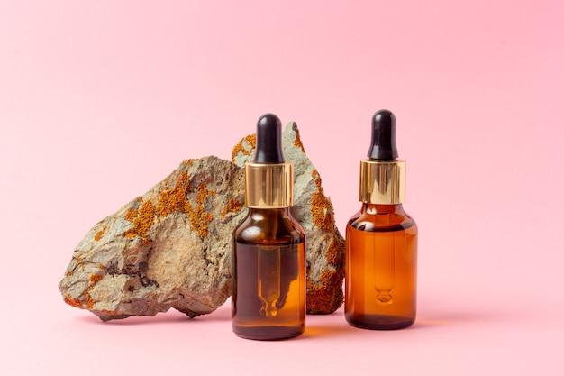 Obok kamienia stoi bursztynowa butelka na olejki eteryczne i kosmetyki.