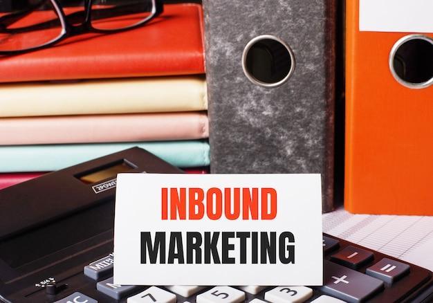 Obok pamiętników i folderów z dokumentami na kalkulatorze znajduje się biała karta z napisem inbound marketing