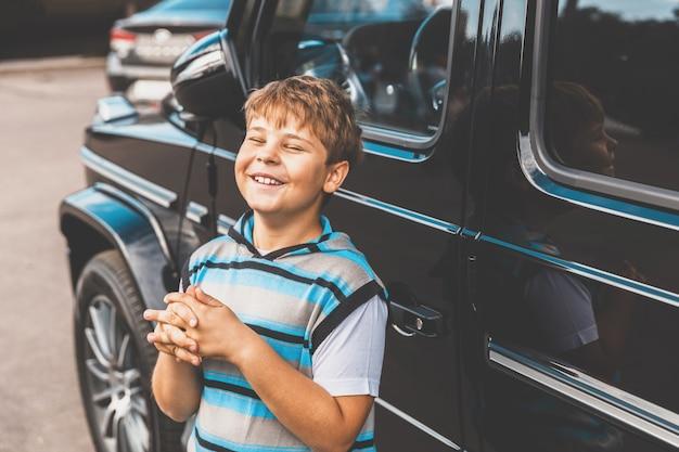 Obok samochodu stoi chłopiec w pasiastym swetrze