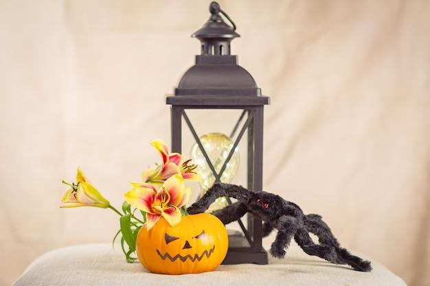 Obok zabytkowej lampy siedzi czarny kudłaty pająk z czerwonymi oczami, dynia halloween i kwiat lilii.
