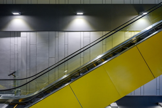 Obok żółtych schodów ruchomych z lampami