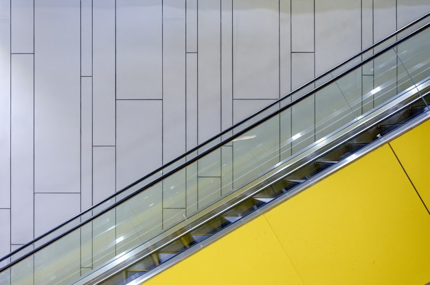 Obok żółtych schodów ruchomych z oświetleniem na ścianie