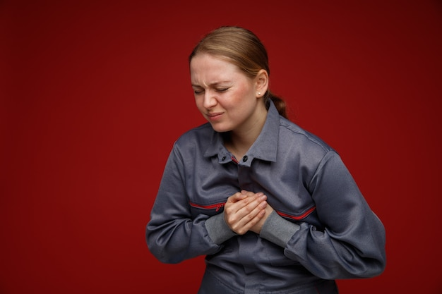 Obolała młoda blondynka inżynier w mundurze, trzymając ręce na klatce piersiowej z zamkniętymi oczami