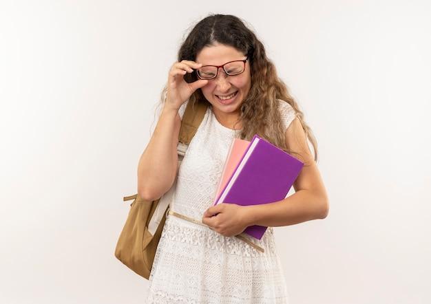 Obolała młoda ładna uczennica w okularach i torbie z plecami trzymająca książki i okulary z zamkniętymi oczami cierpiącymi na ból oczu na białym tle z miejscem na kopię