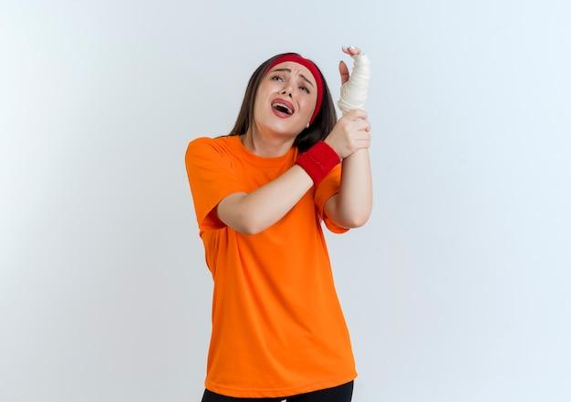 Obolała młoda sportowa kobieta nosząca opaskę i opaski na nadgarstek, trzymając ranny nadgarstek zawinięty w bandaż, patrząc w górę na białym tle