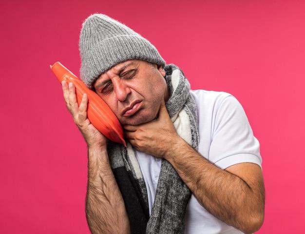 Obolały dorosły chory kaukaski mężczyzna z szalikiem na szyi w zimowej czapce kładzie rękę na szyi i trzyma butelkę z gorącą wodą odizolowaną na różowej ścianie z kopią przestrzeni