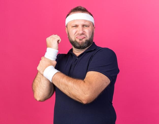 Obolały dorosły słowiański sportowy mężczyzna noszący opaskę i opaski trzymające rękę odizolowaną na różowej ścianie z kopią przestrzeni