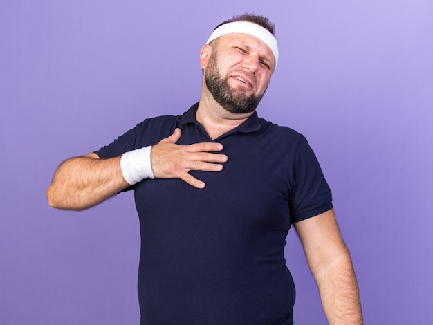 Obolały dorosły słowiański sportowy mężczyzna noszący opaskę na głowę i opaski, kładący rękę na klatce piersiowej odizolowany na fioletowej ścianie z kopią miejsca