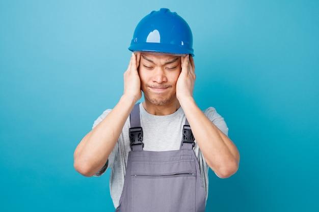 Obolały młody pracownik budowlany w kasku i mundurze, trzymając ręce na głowie z zamkniętymi oczami