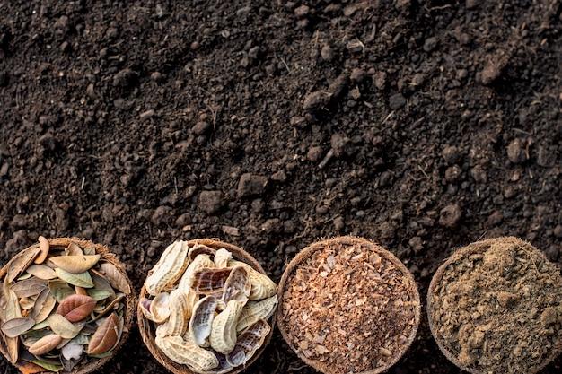 Obornik, trociny, suche liście, łupiny orzechowe umieszczone na gliniastym podłożu.