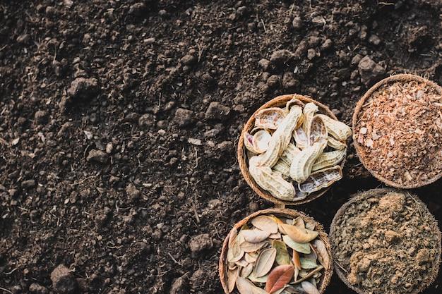 Obornik, trociny, suche liście, muszle orzechowe umieszczone na gliniastej ziemi.