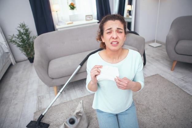 Obowiązki domowe. nastolatka trzymająca papierową chusteczkę źle wyglądająca i nie radząca sobie z czyszczeniem dywanu cierpiąca na silną alergię na kurz
