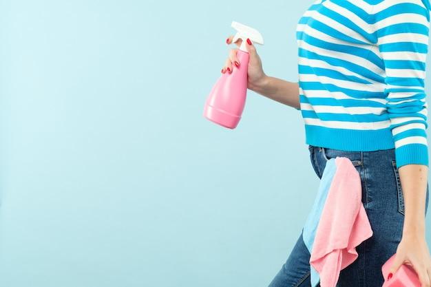 Obowiązki domowe. zorganizowana gospodyni domowa. kobieta trzyma atomizer i gąbkę z szmatką w kieszeni. skopiuj miejsce na niebieskiej ścianie.