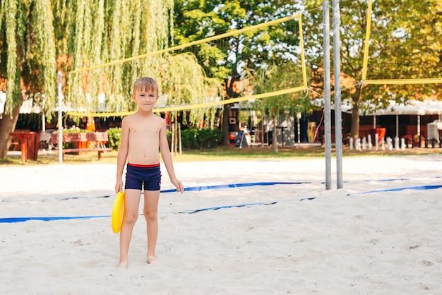 Obóz letni. ładny mały chłopiec bawi się z frisbee na zewnątrz. szczęśliwe dziecko, zabawy na plaży w słoneczny dzień.