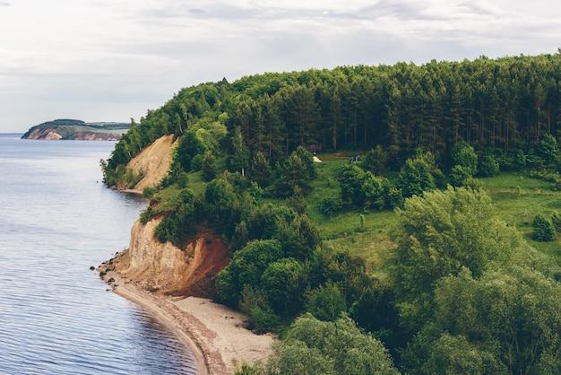 Obóz na brzegu rzeki w sosnowym lesie