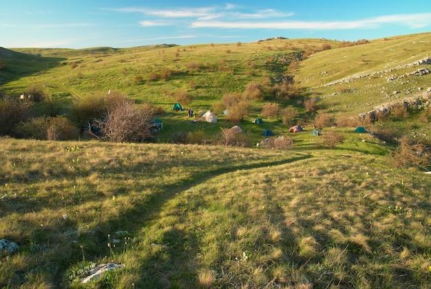 Obóz namiotowy na wzgórzach i błękitnym niebie.