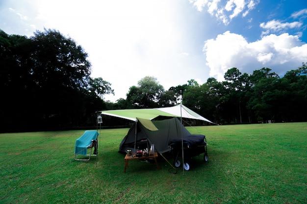Obozować i namiot na zielonej trawie przy lasem na górze
