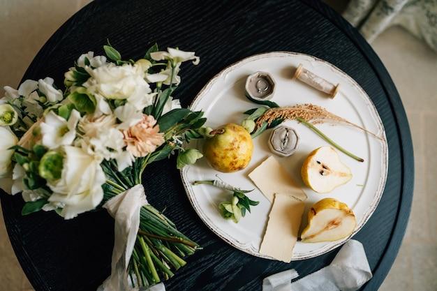 Obrączka leży w pudełku na białym talerzu obok gruszek i zielonych gałązek talerz z bukietem
