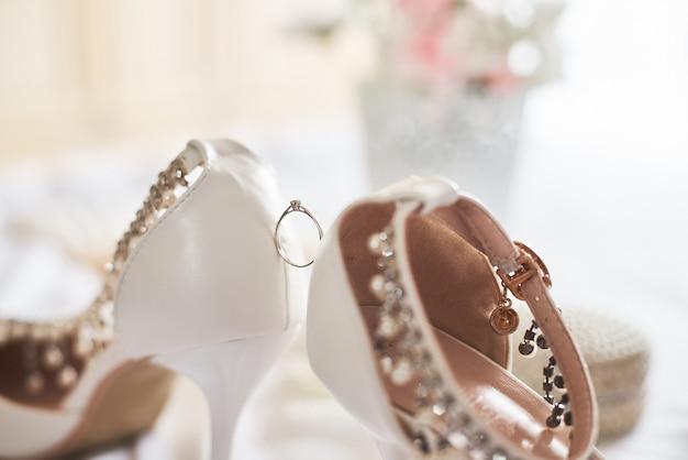 Obrączka ślubna pomiędzy białymi butami ślubnymi.