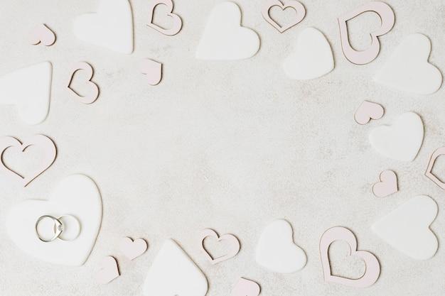 Obrączki na białym kształcie serca nad betonowym tłem